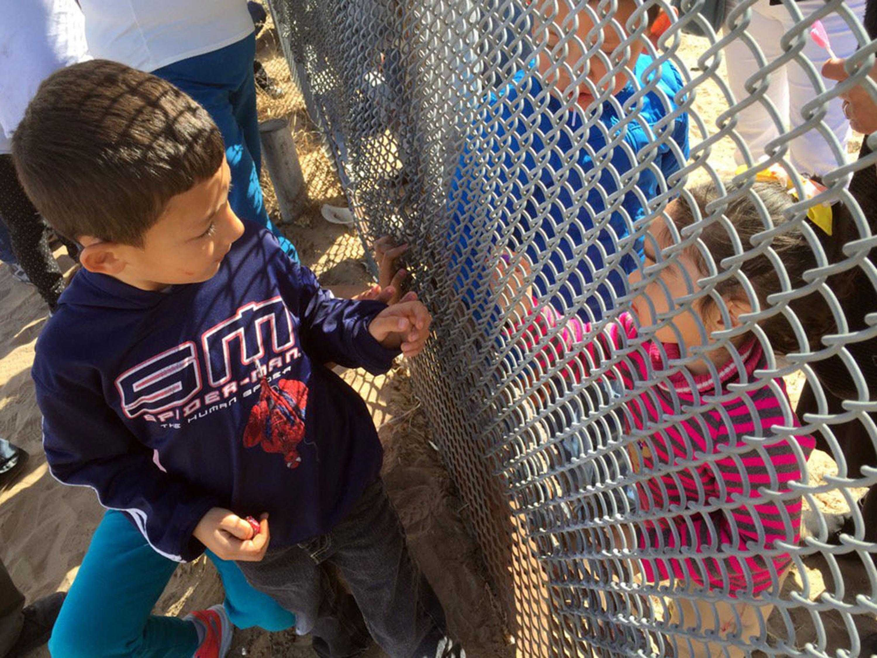 Families and boarder residents who live on both sides of the U.S.-Mexico border gathered last year along a chain link fence separating the two countries. Baxter says