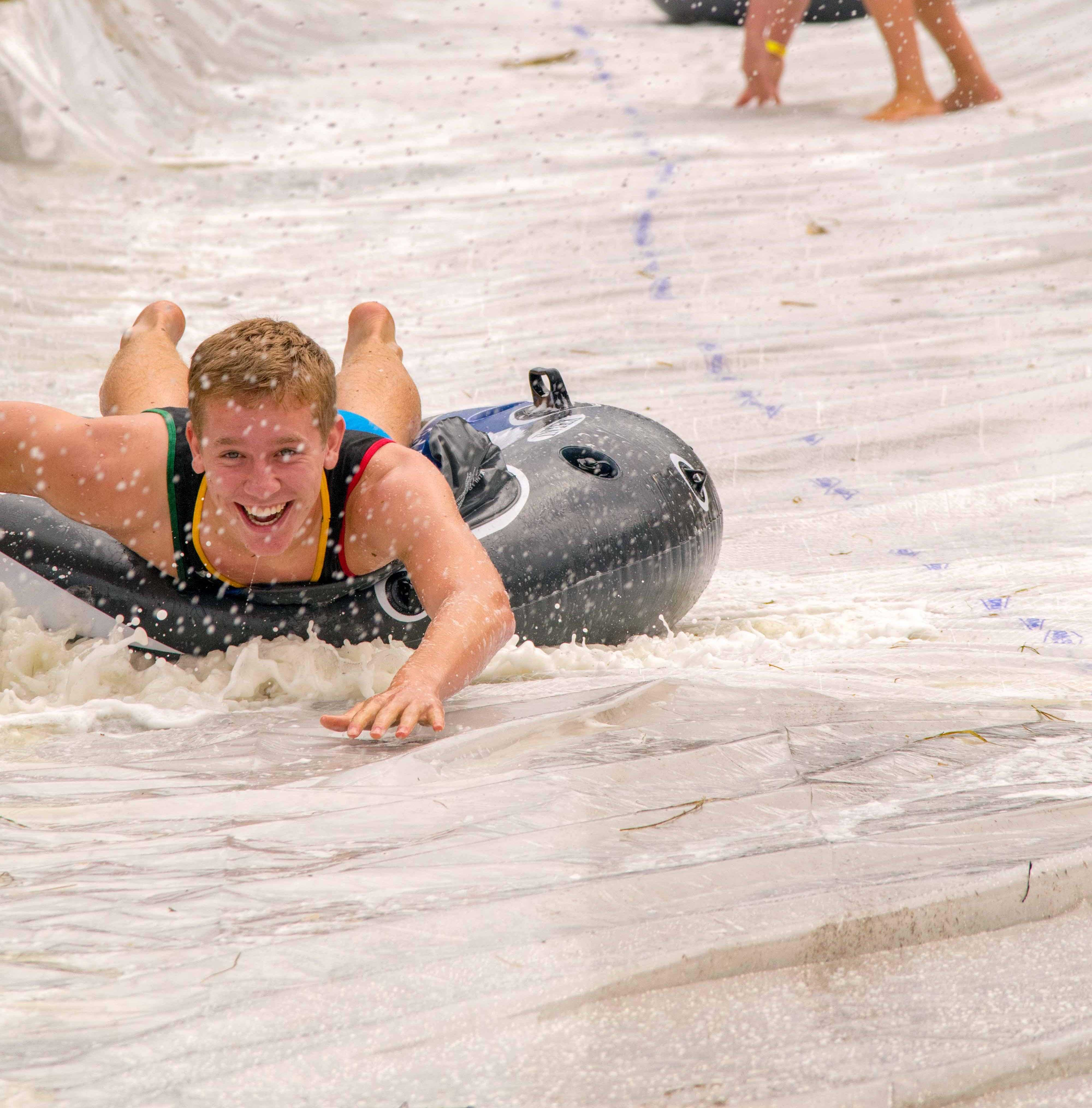 Jace Jirak, sophomore potential business major., slides down the 200 foot long slip and slide. The slide was made of hay bails and plastic sheets