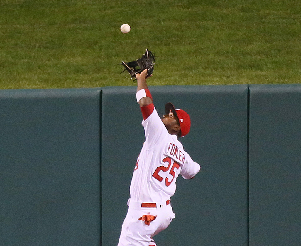 St. Louis Cardinals' center fielder, Dexter Fowler, catches a fly ball off the wall, hit by the Chicago Cubs' Javier Baez in the ninth inning