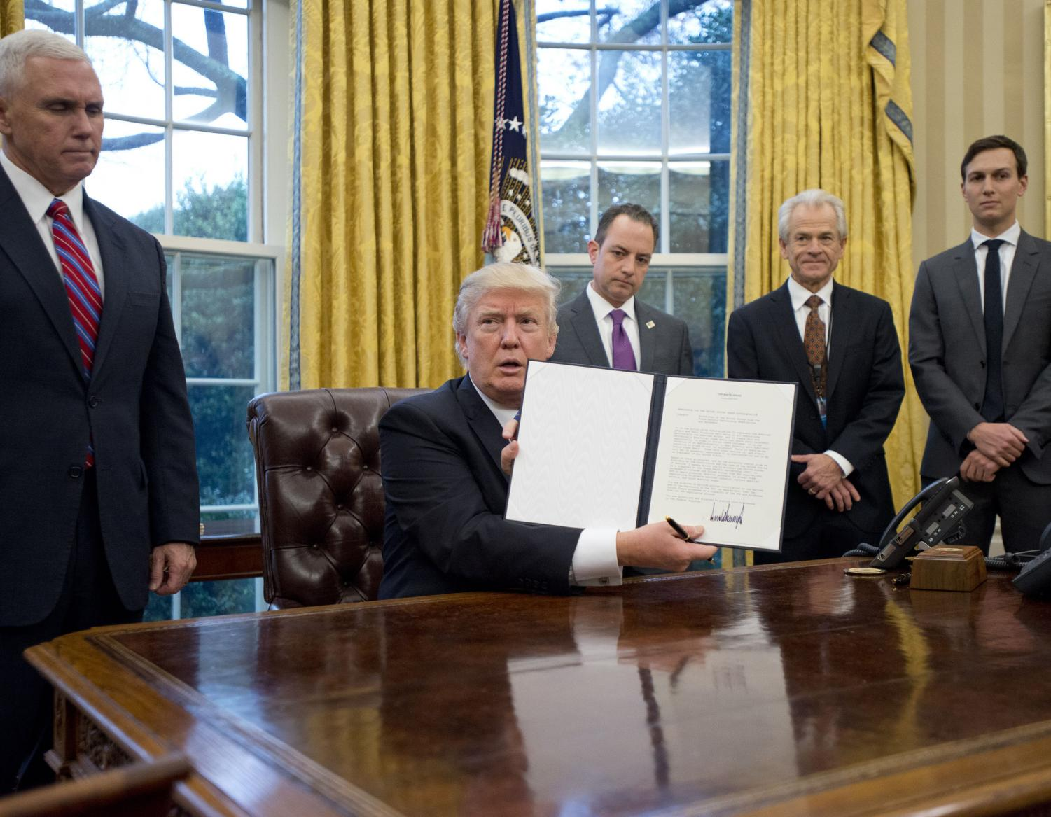 President Trump with his executive order to withdraw from the Trans Pacific Partnership on Jan. 23, 2017.