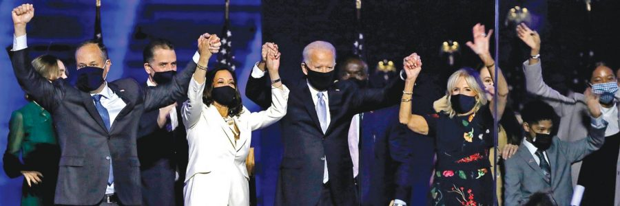 Vice President-elect Kamala Harris and President-elect Joe Biden triumphantly raise their hands after declaring victory on Saturday, Nov. 7.