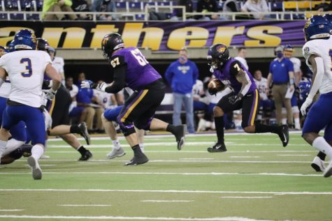 UNI graduate transfer running Dom Williams carries the ball with offensive linemen Erik Sorensen leading the way. Williams, a transfer from the University of Kansas, ran for 35 yards in the Panther