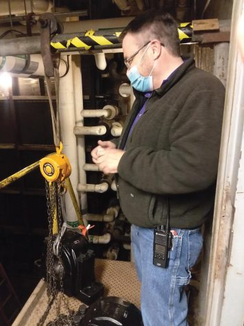 Mike Henney stands next to one of the 250 pound bearings to be installed.