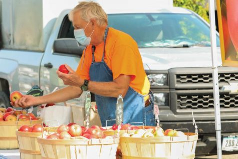 Vendor at the College Hill Farmers Market handing out food to customers.