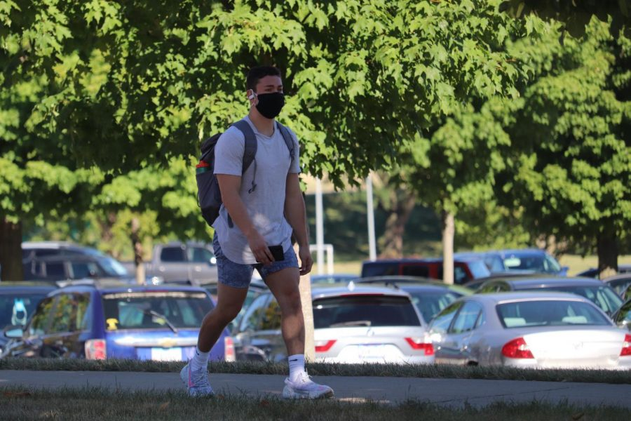 Un estudiante con màscara camindo.