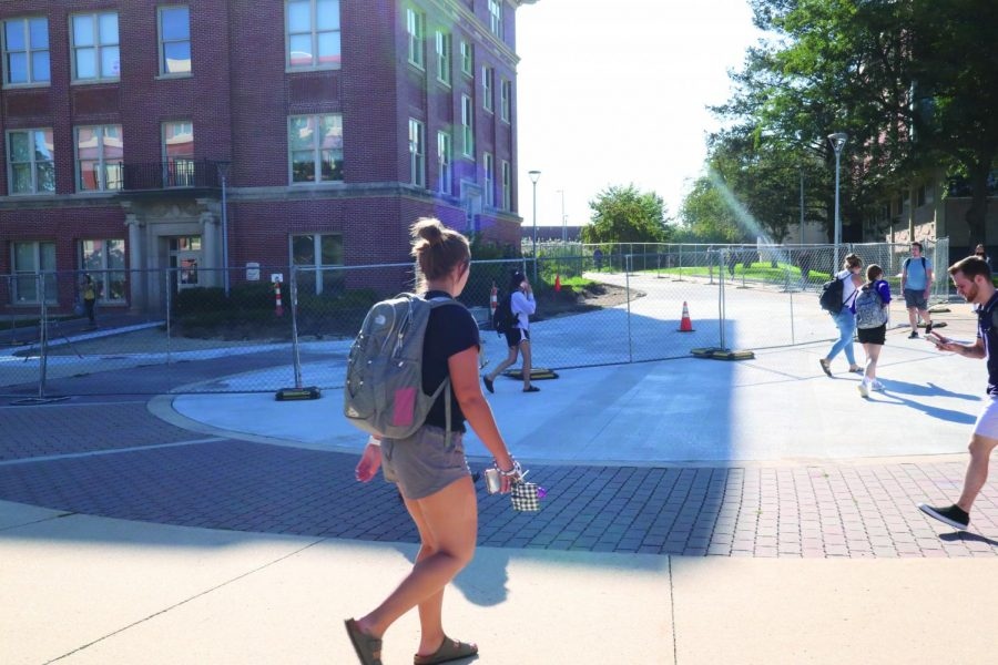Students walk by the fence separating the construction zone on the north side of Wright Hall between classes. Construction by Wright should be done within two weeks.